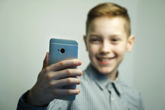 Teenage serious boy with stylish haircut taking selfie on smartphone. Teenage serious boy in office shirt with stylish haircut taking selfie on smartphone in Stock Photos