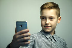 Teenage serious boy with stylish haircut taking selfie on smartphone. Teenage serious boy in office shirt with stylish haircut taking selfie on smartphone in Royalty Free Stock Images