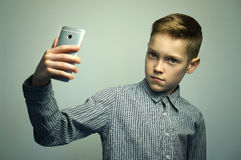 Teenage serious boy with stylish haircut taking selfie on smartphone. Teenage serious boy in office shirt with stylish haircut taking selfie on smartphone in Stock Image