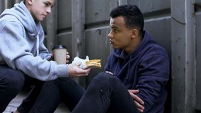 Teenage sharing lunch with afro-american friend, support in hard situation. Stock photo stock image