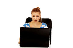 Teenage shocked woman with laptop sitting behind the desk Royalty Free Stock Image