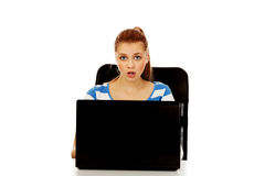 Teenage shocked woman with laptop sitting behind the desk Royalty Free Stock Images