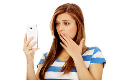 Teenage shocked woman reading a message on mobile phone Royalty Free Stock Photography