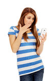 Teenage shocked woman reading a message on mobile phone Royalty Free Stock Photos