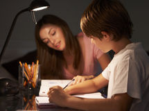 Teenage Sister Helping Younger Brother With Studies At Desk In Bedroom In Evening Stock Photos