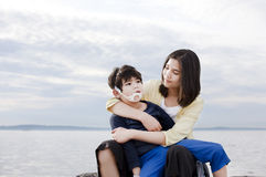 Teenage sister holding disabled brother Stock Photography