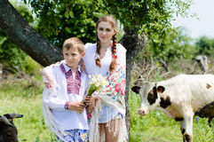 Teenage sister and little brother by cow herd Stock Photos