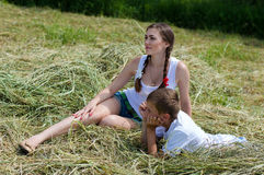 Teenage sister and little brother sitting on hay Stock Photo