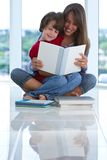 Teenage sister reads a book to little brother Royalty Free Stock Images