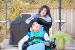 Teenage sister taking care of disabled brother in wheelchair out Stock Photography