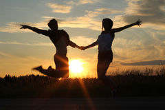 Teenage sisters, doing exercises at sunset Royalty Free Stock Photo
