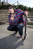 Teenage skateboarder crouching down Royalty Free Stock Images