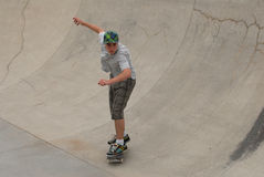 Teenage skateboarder in pipe. Teenage skateboarder riding in cement half pipe Stock Photography