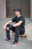 Teenage skateboarder sitting Royalty Free Stock Image