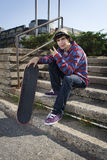 Teenage skateboarder sitting on stairs Royalty Free Stock Photography