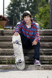 Teenage skateboarder sitting on stairs Royalty Free Stock Photos