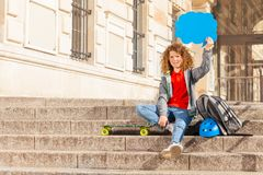 Teenage skateboarder with speech bubble over head. Cute teenage boy with skateboard and backpack, sitting on the stairs outdoors, holding blue blanked speech Royalty Free Stock Photo