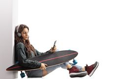 Teenage skater girl with a longboard leaning against a wall and Royalty Free Stock Image
