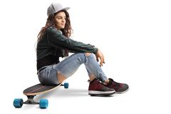 Teenage skater girl sitting on a longboard Royalty Free Stock Images