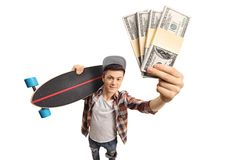 Teenage skater holding a longboard and showing money bundles. Isolated on white background Stock Photo