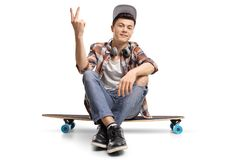 Teenage skater sitting on a longboard and making a peace gesture. Isolated on white background Stock Photography
