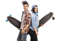 Teenage skaters with longboards with their backs against each ot Royalty Free Stock Image
