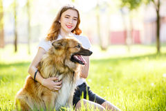 Teenage smiling girl with her dog sitting in park Royalty Free Stock Photography