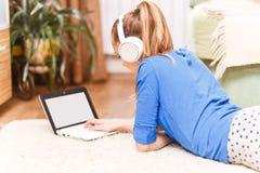Teenage smiling girl using laptop on the floor. Teenage smiling girl with white headphones using laptop on the floor Stock Photo