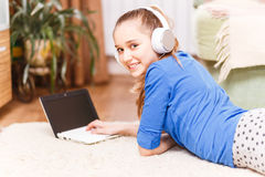 Teenage smiling girl using laptop on the floor Royalty Free Stock Image