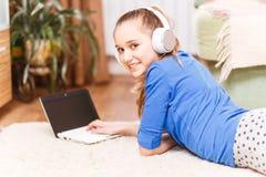 Teenage smiling girl using laptop on the floor. Teenage smiling girl with white headphones using laptop on the floor. Smiling teenager looking into camera Royalty Free Stock Image