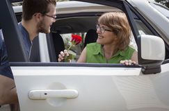 Teenage son handing his mom a red rose in the car. Horizontal image of a teenage son handing his mom a red rose as she is getting out of the car Royalty Free Stock Image