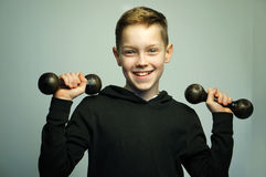Teenage sport boy with dumbbells and stylish haircut, studio shot. Portrait of a handsome teenage sport boy with dumbbells and stylish haircut, softbox lighting Stock Photos