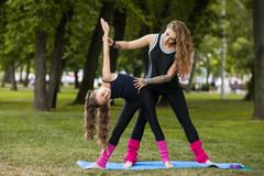 Teenage sport outdoors. Teamwork gymnastics. Yoga training exercise with coach, healthy beauty. Nature background, creative entertainment outside Royalty Free Stock Image