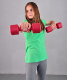 Teenage sportive girl is doing exercises with dumbbells to develop muscles on grey background. Sport healthy lifestyle concept. Sp Stock Photos