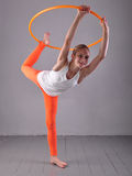 Teenage sportive girl is doing exercises with hula hoop t on grey background. Having fun playing game . Sport healthy lifestyle co. Teenage sportive girl is stock image