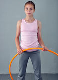 Teenage sportive girl is doing exercises with hula hoop to develop muscle on grey background. Having fun playing game hula-hoop. S Stock Images
