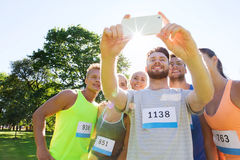 Teenage sportsmen taking selfie with smartphone. Fitness, sport, friendship, technology and healthy lifestyle concept - group of happy sportsmen friends with Stock Images