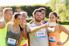 Teenage sportsmen taking selfie with smartphone. Fitness, sport, friendship, technology and healthy lifestyle concept - group of happy sportsmen friends with Stock Photos