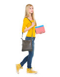 Teenage student girl with books going sideways Royalty Free Stock Photos