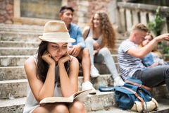 Teenage student girl sitting on stone steps reading a book. Attractive teenage student girl sitting on stone steps with her friends in front of university Stock Photo