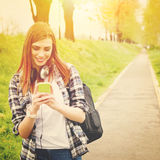 Teenage student girl with smart phone texting Royalty Free Stock Images