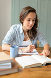 Teenage student girl studying book at home Stock Images