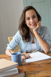 Teenage student girl studying at home smiling. Leaning against table royalty free stock photo