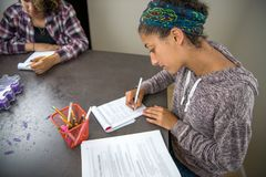 Teenage student girls studying from textbooks and writing notes in notebooks stock images