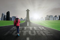 Teenage student go ahead on the road. Young schoolgirl wearing winter clothes and walking on the stree rising upward as an arrow with better future text Royalty Free Stock Photo