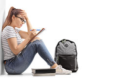 Teenage student having difficulty studying. And leaning against a wall isolated on white background Royalty Free Stock Photos
