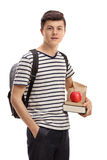 Teenage student holding books and a snack Stock Images