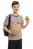 Teenage student holding a paper bag and a sandwich. Isolated on white background royalty free stock image