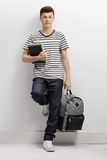 Teenage student leaning against a gray wall Stock Photography