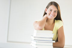 Teenage Student Leaning On Stacked Books In Classroom Royalty Free Stock Images